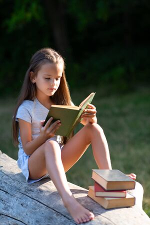 Charming little girl with long brown hair reads book outdoor sitting on tree in summer park or in a forest glade. Child booklover