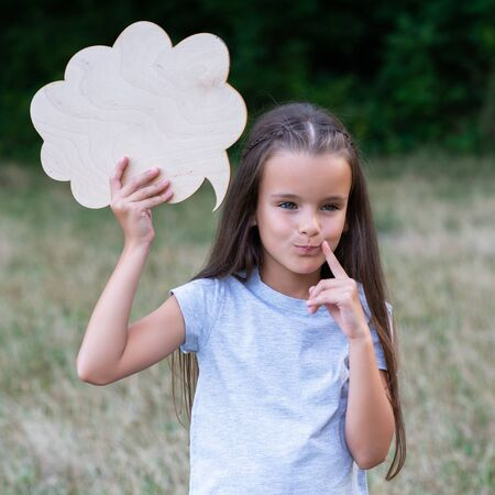 Pretty thinking little girl posing summer nature outdoor with cloud of thoughts (like in comic book). Kids portrait. Emotions, feeling and thoughts of child