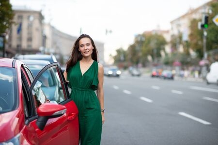 Fashion model wearing green overall posing outdoor next to her red car on the road. Young beautiful brunette caucasian woman driver. Beautiful girl, urban portrait.