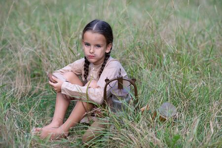 Pretty little girl with long pigtails and beautiful dirty face in summer forest and meadow holding vintage flask. Orphan, child of war, poverty, hunger, famine, poor destitute kid. Stock Photo