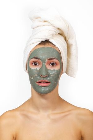 Beautiful cheerful girl applying facial clay mask. Young woman and beauty treatments over white background. Pampering, youth, anti-aging, body care spa theme. Female face with cosmetics mask Imagens