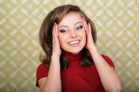 Young smiling ecstatic woman looking at camera in room with vintage wallpaper, retro stylization 60-70s.