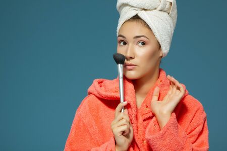Young attractive woman putting blush on her cheekbones over blue background. Charming girl makes morning beauty treatments and make-up