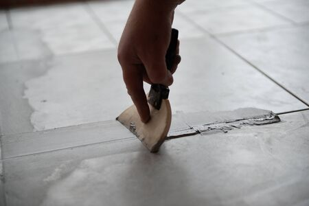 Tiler laying the ceramic tile on the floor. Professional worker makes renovation. Construction. Hands of the tiler. Home renovation and building new house Stock Photo