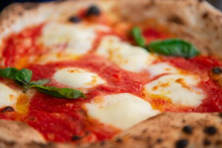 Delicious tasty traditional italian Margaret pizza (Margarita), mozzarella cheese, tomatoes, basil and crispy dough cooked in the oven in restaurant or pizzeria, detail, soft focus