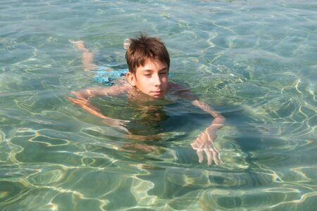 Cheerful handsome teen boy swiming in turquoise blue sea water above water surface and underwater. Beach, summer vacation, teenage lifestyle, recreation.