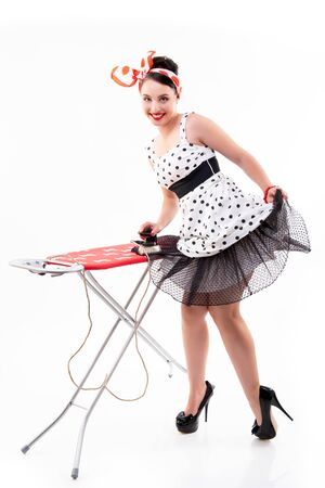 Pinup girl irons her dotted dress and happy smiling. Retro portrait of young cheerful woman in pin-up style, vintage stylization, studio shot over white background.