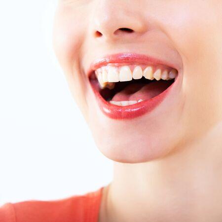 Femme qui rit, bouche féminine avec de grandes dents sur fond blanc. Beau sourire sain. Santé des dents, blanchiment, prothèses et soins.