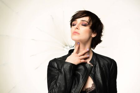 Beautiful young woman with short dark hair posing at studio in leather clothes over lightning equipment . Pretty brunette girl, studio portrait.