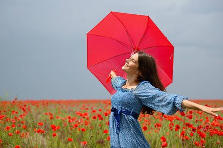 Young beautiful woman wearing blue summer drees holding red umbrella in poppy field. Charming girl walks before the rain, nature outdoor