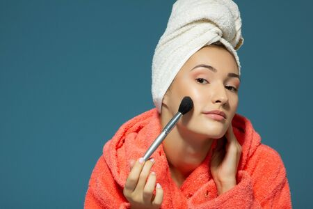 Young attractive woman putting blush on her cheekbones, blue background. Charming girl makes morning beauty treatments and make-up with a towel on his head after a shower Foto de archivo