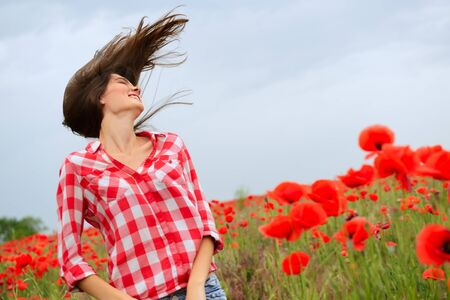 Young beautiful woman walking at poppy field. Happy girl dancing among blooming red flowers, spring nature outdoor Zdjęcie Seryjne
