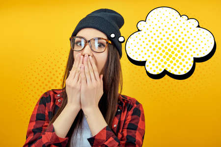 Excited surprised young woman covers hands open mouth over yellow background with speech bubbles. Emotional female portrait, creative collage in Pop Art style.