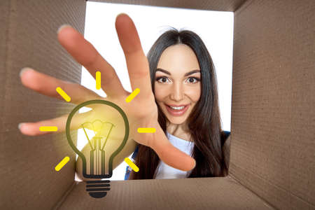 Happy girl opening postal package with light idea cartoon lamp inside. Excited young woman finds an idea bulb in cardboard box. Gift, present, delivery, shipment, sale, brilliant solution.