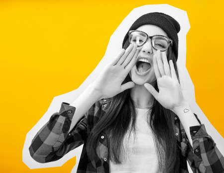 Girl screaming like in megaphone holding hands near her face with open mouth, collage in magazine style. Young woman touts everyone over yellow background.
