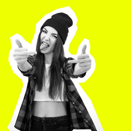 Girl in jeans, checked shirt and hat showing middle fingers over vivid yellow background, collage in magazine style. Impertinent behaviour. Hipsters. Provocation.