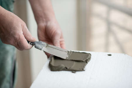 A man putsglue with putty knife on foam to stick it to the ceiling. seiling mounting. A man glues foam. Ceiling insulation. Warming. Repair in the house. Male hands with tools. DIY repair