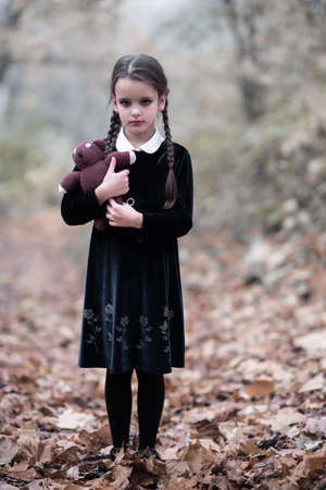 Beautiful little girl with long brunette hair, dressed in dark velvet dress walks in fall forest with handmade bear toy. Halloween horror, ghost or spirit of child in twilight