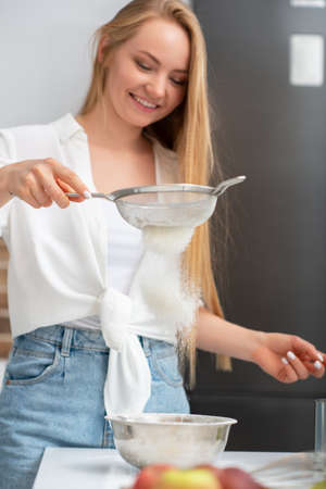 Young woman standing in the kitchen at home and cooking with enjoyment bakery products of flour, milk, cocoa, sugar and fruits. Funny portrait of happy girl chef sifts flour Foto de archivo - 154867946