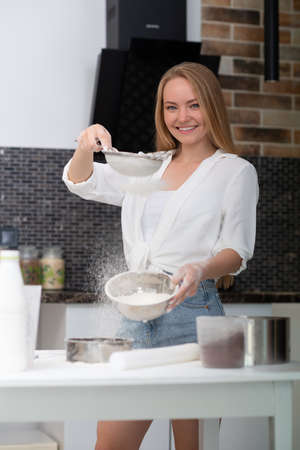 Young woman standing in the kitchen at home and cooking with enjoyment bakery products of flour, milk, cocoa, sugar and fruits. Funny portrait of happy girl chef sifts flour Foto de archivo - 154867947