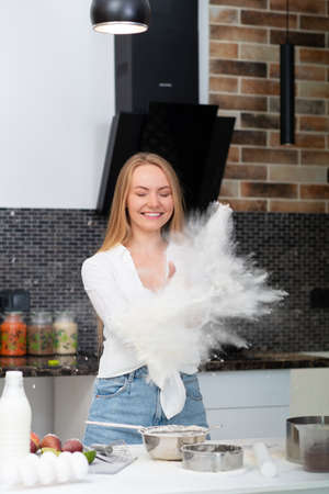 Young woman standing in the kitchen at home and cooking with enjoyment bakery products of flour, milk, cocoa, sugar and fruits. Funny portrait of happy girl chef