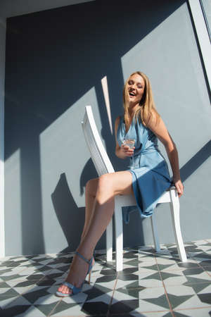Beautiful fashion woman wearing light blue summer dress posing indoor with glass of alcohol drink and happy smiling, full length portrait.