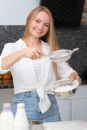 Young woman standing in the kitchen at home and cooking with enjoyment bakery products of flour, milk, cocoa, sugar and fruits. Funny portrait of happy girl chef sifts flour Foto de archivo - 154868004