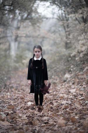 Beautiful little girl with long brunette hair, dressed in dark velvet dress walks in fall forest with handmade bear toy. Halloween horror,  ghost or spirit of child in twilight Foto de archivo - 154868015
