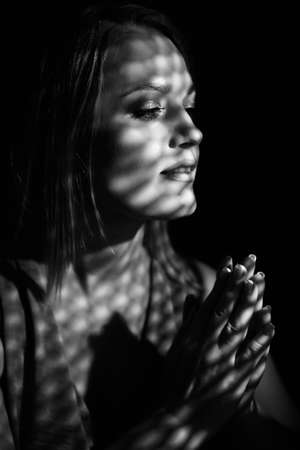 Beautiful woman confesses in the confessional, black and white. Praying woman, fine art portrait with interesting ligth and shadow pattern. Absolution. Foto de archivo