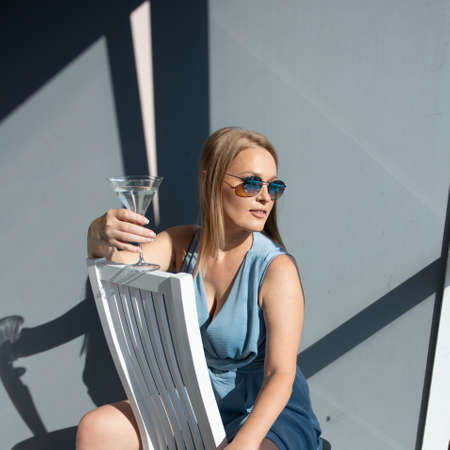 Beautiful fashion woman wearing light blue summer dress and sun glasses posing indoor with glass of alcohol drink, full length portrait. Foto de archivo - 154868036