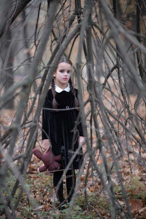 Beautiful little girl with long brunette hair, dressed in black velvet dress walks in fall forest with handmade bear toy. Halloween horror,  ghost or spirit of child in twilight Foto de archivo - 154868076