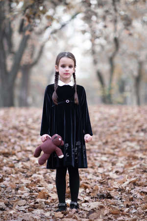 Beautiful little girl with long brunette hair, dressed in dark velvet dress walks in fall forest with handmade bear toy. Halloween horror,  ghost or spirit of child in twilight Foto de archivo - 154868085
