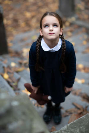 Beautiful sad little girl with with pigtails, dressed in dark blue standing near mystic abandoned building with gothic stairs and holding handmade bear toy. Halloween horror, ghost or spirit of child. Loneliness, depression Foto de archivo - 154868104