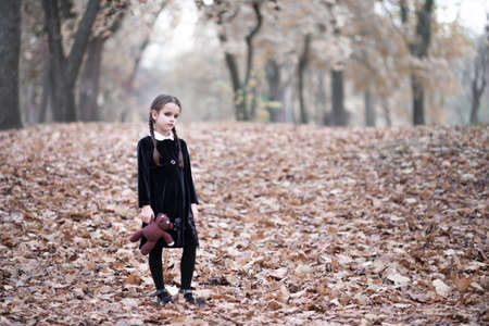 Beautiful little girl with long brunette hair, dressed in dark velvet dress walks in fall forest with handmade bear toy. Halloween horror,  ghost or spirit of child in twilight Foto de archivo - 154868118