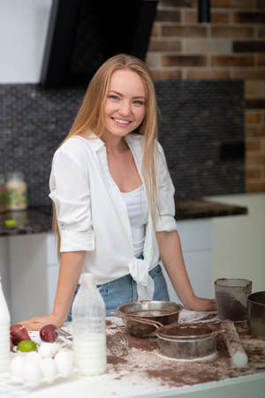 Young woman standing in the kitchen at home and cooking with enjoyment bakery products of flour, milk, cocoa, sugar and eggs. Funny portrait of happy girl chef Foto de archivo