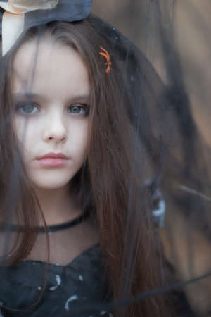 Llittle girl dressed in a witch dress and hat walks in fall forest among the web with spiders, soft focus. Halloween horror. Witches in darkness Foto de archivo