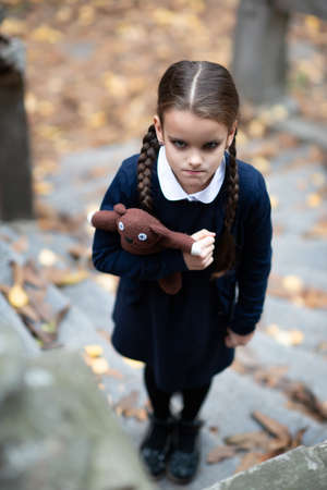 Beautiful angry little girl with with pigtails, dressed in dark blue standing near mystic abandoned building with gothic stairs and holding handmade bear toy. Halloween horror, ghost or spirit of child. Loneliness, depression