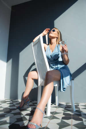 Beautiful fashion woman wearing light blue summer dress and sun glasses posing indoor with glass of alcohol drink, full length portrait. Foto de archivo