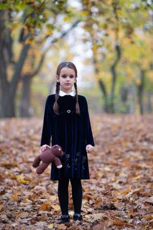 Beautiful little girl with long brunette hair, dressed in dark velvet dress walks in fall forest with handmade bear toy. Halloween horror,  ghost or spirit of child in twilight Foto de archivo - 154868175