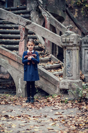 Beautiful little brunette girl with with pigtails, dressed in dark blue standing near mystic abandoned building with gothic stairs and holding handmade bear toy. Halloween horror, ghost or spirit of child in twilight Foto de archivo - 154868176