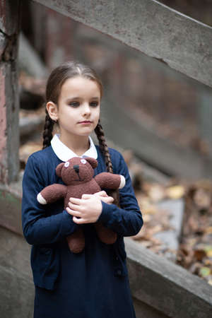 Beautiful sad little girl with with pigtails, dressed in dark blue standing near mystic abandoned building with gothic stairs and holding handmade bear toy. Halloween horror, ghost or spirit of child. Loneliness, depression Foto de archivo - 155047329