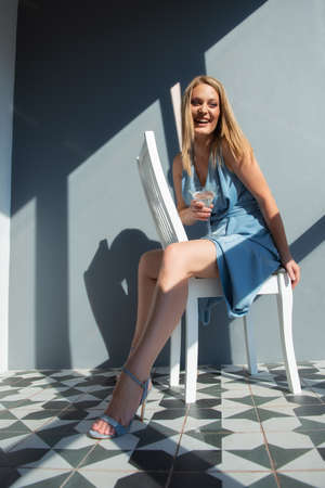 Beautiful fashion woman wearing light blue summer dress posing indoor with glass of alcohol drink and happy smiling, full length portrait. Foto de archivo - 155047330