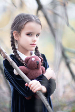 Beautiful little girl with long brunette hair, dressed in black velvet dress walks in fall forest with handmade bear toy. Halloween horror,  ghost or spirit of child in twilight Foto de archivo