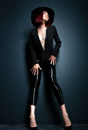 Beautiful fashion woman with perfect body. Portrait of beautiful girl wearing black blazer, latex tight pants and hat posing in studio over deep  gray background Foto de archivo - 155047335