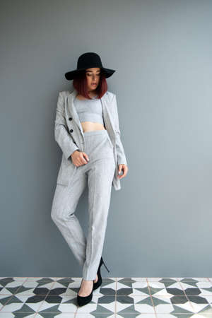 Beautiful fashion woman. Full length portrait of beautiful girl wearing light gray suit and black hat posing indoor over deep  gray wall