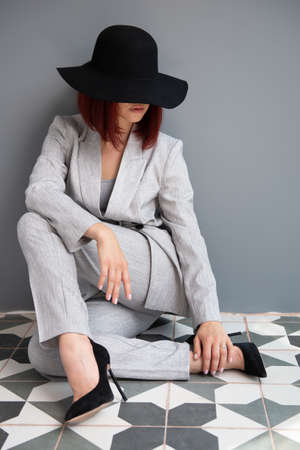 Beautiful fashion woman. Full length portrait of beautiful girl wearing gray suit and black hat sitiing on the floor at home