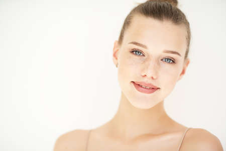 Portrait of beautiful woman with clean skin, youth concept, beauty treatment. Cheerful teen girl, beauty female face happy smiling and looking at camera over white background Foto de archivo