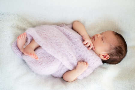 New born baby girl sleeps at home and smiling in a dream. Cute little kid's portrait