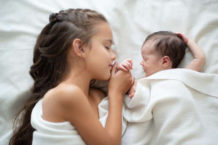 Little girl sleeps with her new born baby sister at home. Cute children's portrait