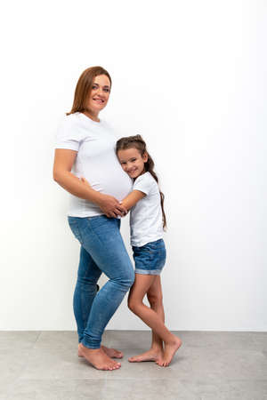 Beautiful smiling girl hugs her pregnant mother with big belly.